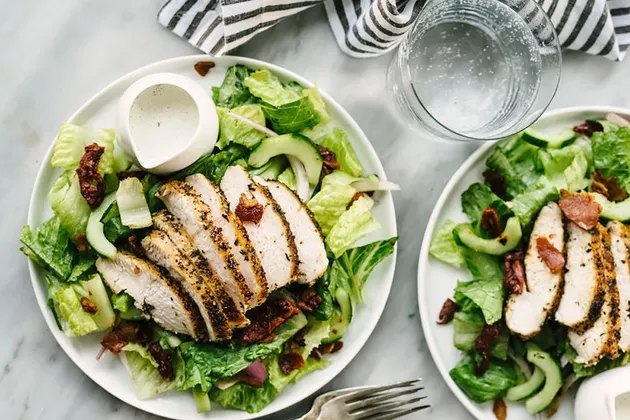 healthy chicken recipe of green salad topped with grilled chicken