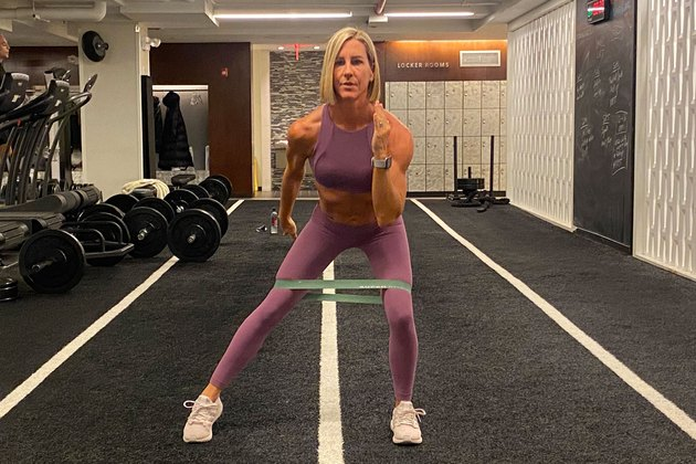fitness instructor kira stokes demonstrates the Squat With Tap-Out glute exercise with a resistance band