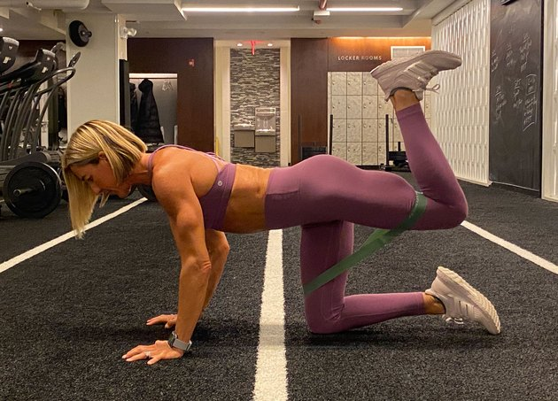 fitness instructor kira stokes demonstrates the Bent-Knee Donkey Kick glute exercise with a resistance band