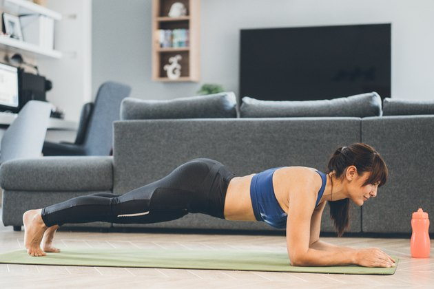 Woman performing side plank exercise while working from home.