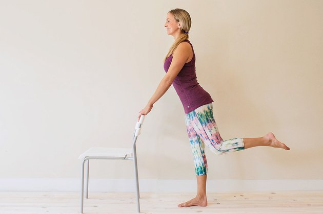 Woman demonstrating how to do a standing hip extension for an at-home barre workout