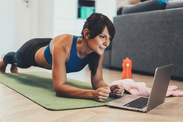 Woman holding plank while watching laptop