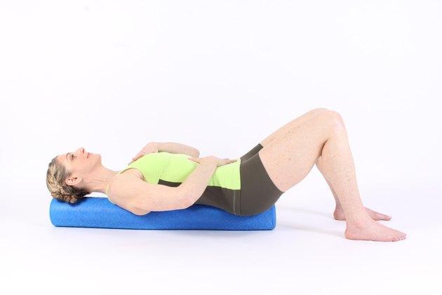 woman lying on foam rollers demonstrating rebalance exercise for MELT method