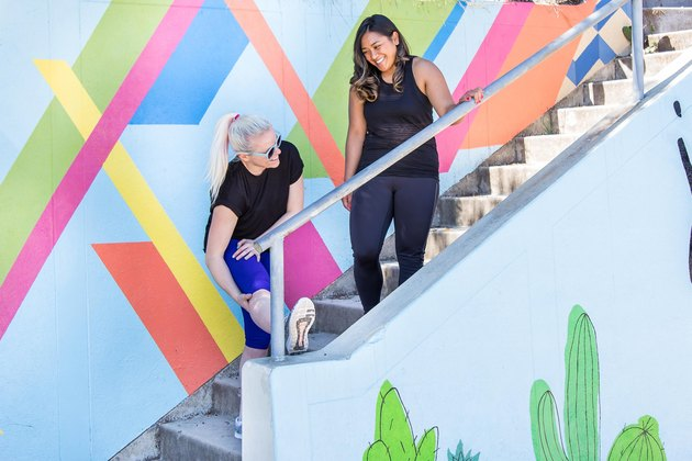 two women stretching on a colorful staircase after walking