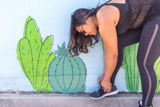 woman tying her shoe after walking while next to a colorful mural