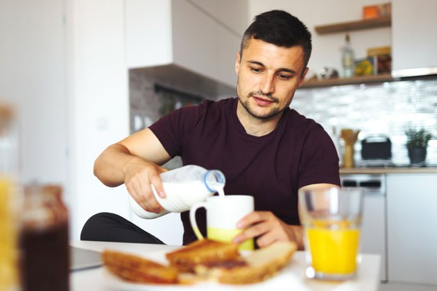 Man pouring glass of milk at breakfast.