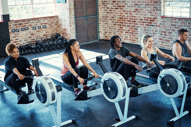 Women and men in gym on rowing machines
