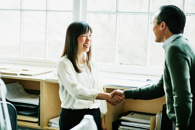 Woman and man meeting shaking hands