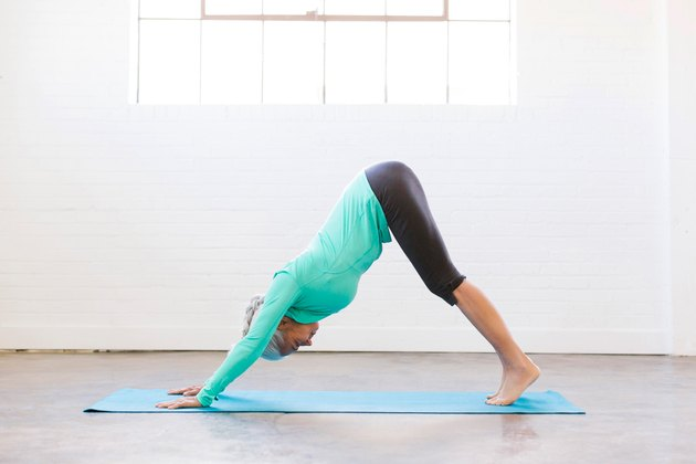 Woman doing Downward Facing Dog standing yoga pose for balance