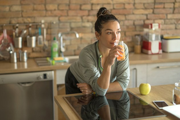 Woman drinking juice in her kitchen