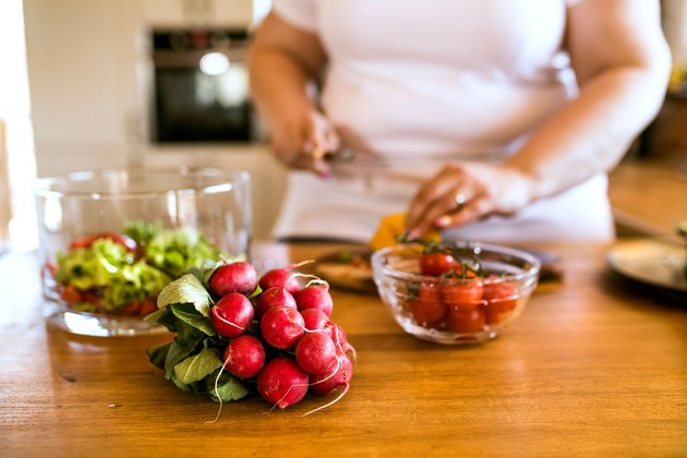 Woman cutting fruit while meal prepping to safely lose 20 pounds in one month