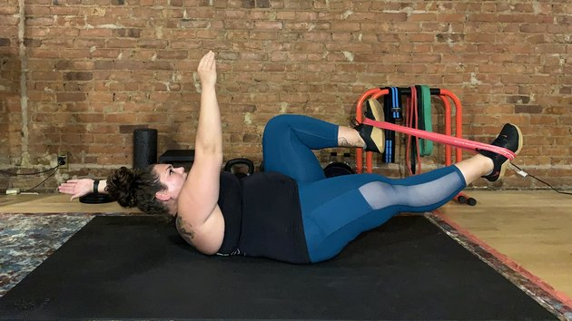 Woman doing a resistance band ab workout at the gym