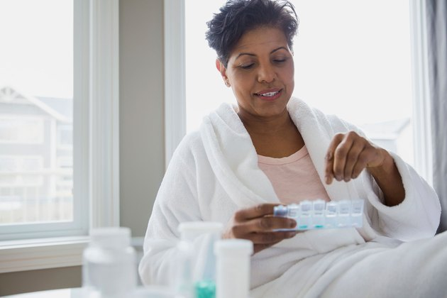 Middle-aged woman in white robe taking morning pills from pill case