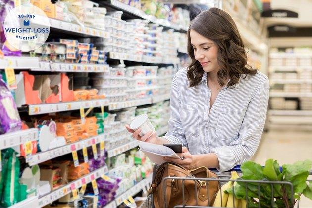 Young woman checks yogurt ingredients while grocery shopping
