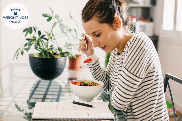 Woman eating breakfast and reading food journal