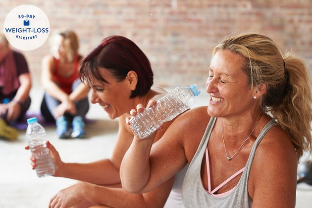 Two women laughing and drinking from water bottles after exercising to lose weight