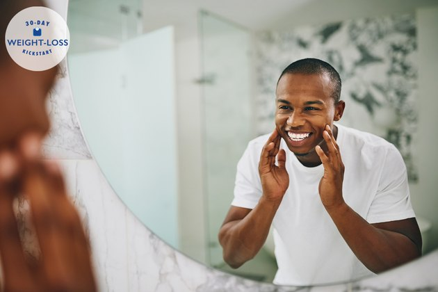 A smiling man looking at his reflection in the bathroom mirror after losing weight