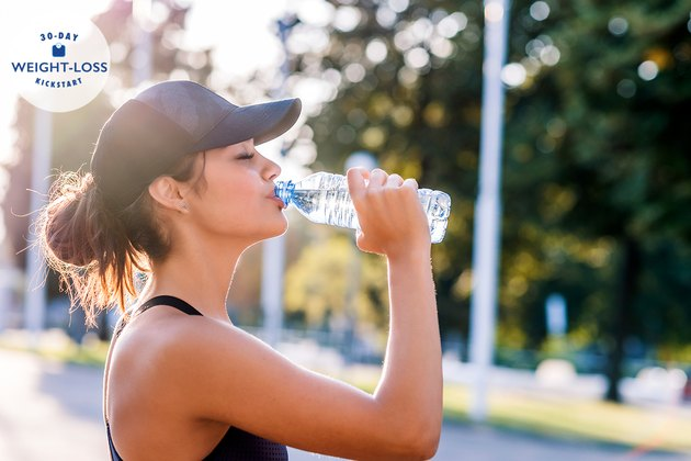 A woman doing intermittent fasting drinking water outside after a workout