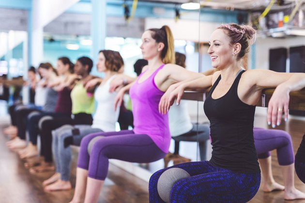 Women having fun in barre exercise class