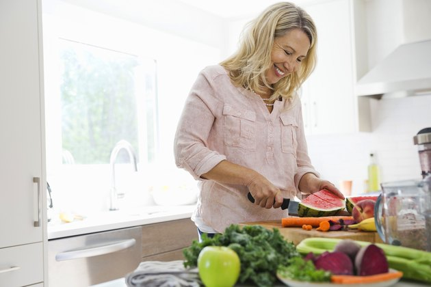 woman cutting fruits and vegetables in the kitchen
