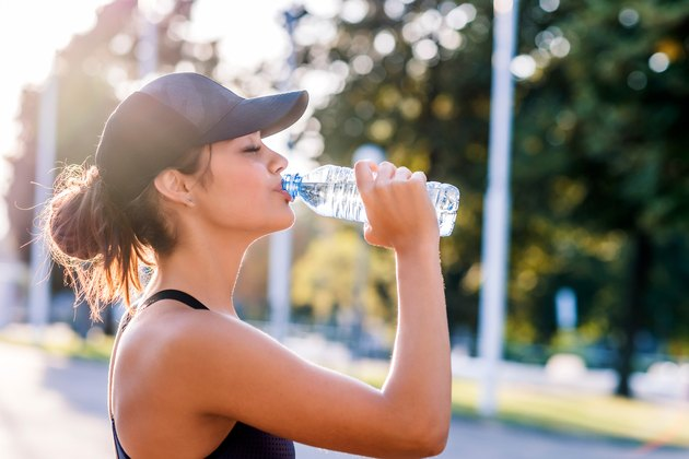 woman drinking water in the morning after workout