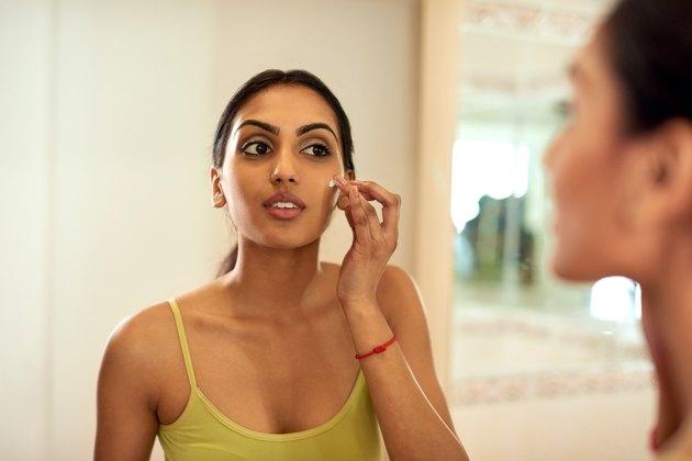 Woman applying moisturizer to skin.