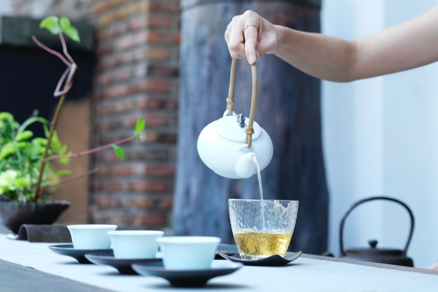 hand pouring tea into glass