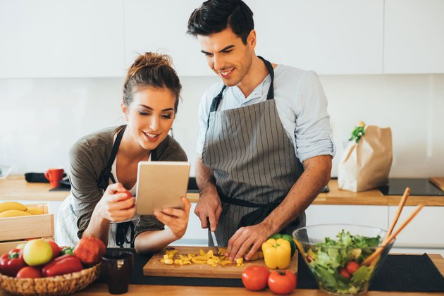 Woman and man in kitchen using cooking tips on ipad