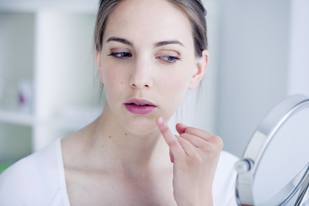 Woman looking at herself in the mirror for cold sore