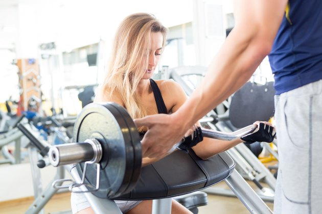 Woman at the gym with a personal trainer doing biceps curls
