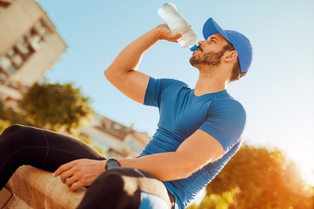 Thirsty athlete man drinking water