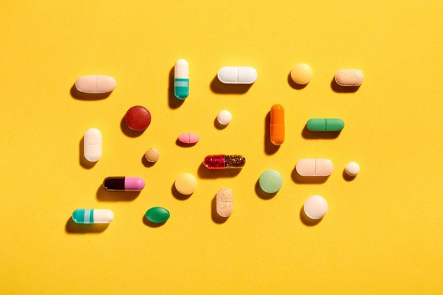 Colorful variety of vitamin and supplement pills on a yellow background