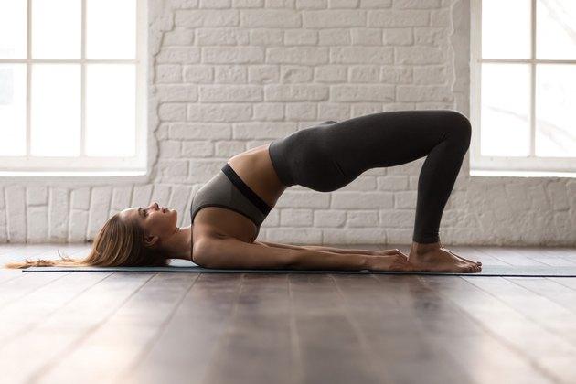 Woman doing bridge pose in well-lit studio