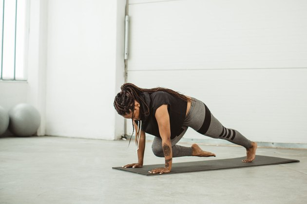 Woman doing mountain climbers or a knee-to-arm plank