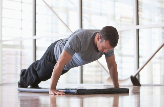 Man holding a plank over a mat in the gym.