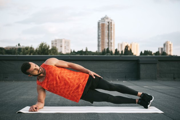 Man doing a side plank on urban rooftop outside.