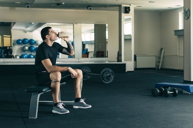 Man drinking muscle-building protein powder supplement after a workout
