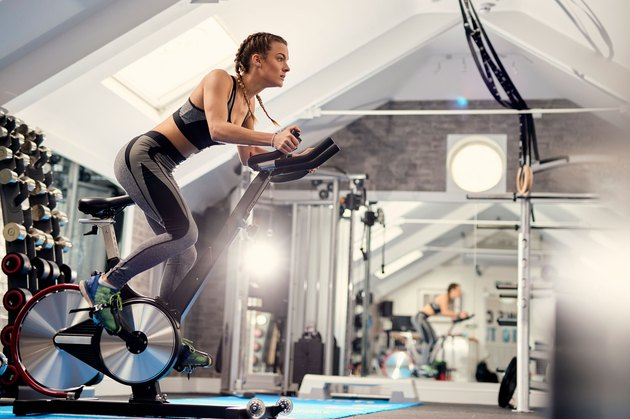 Woman using stationary indoor exercise bike for fitness