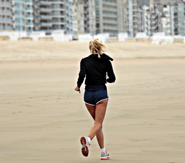 Woman running on the beach wearing women's workout shorts