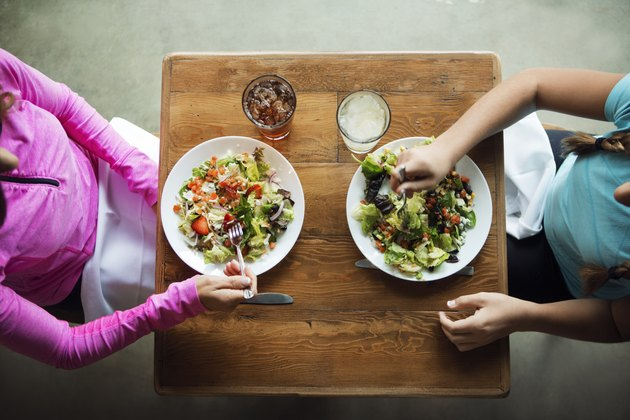 Overhead shot of two women eating salads at a restaurant practicing portion control