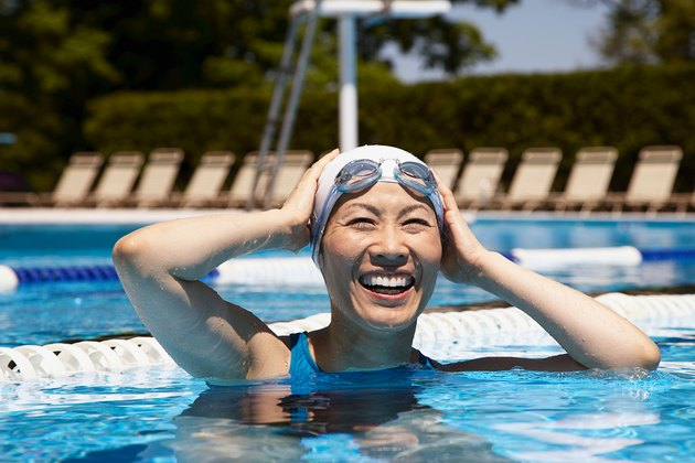 Woman in outdoor lap pool with swim cap and goggles
