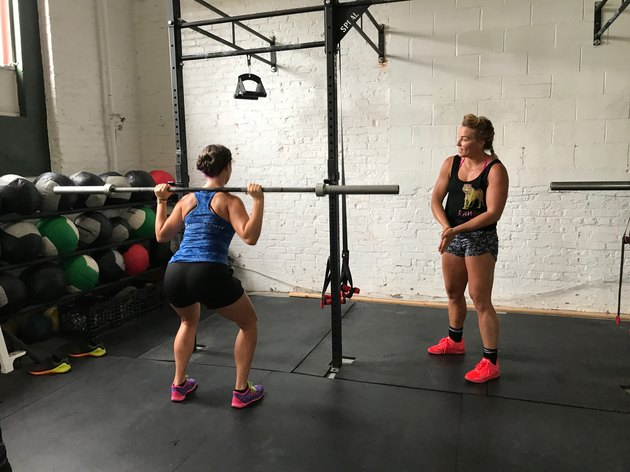 Jen Sinkler trains a woman on proper back squat technique