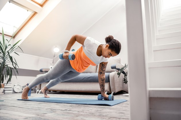 Woman doing at-home workouts using weights in living room
