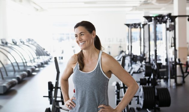 Happy woman in gym next to weights and treadmills.