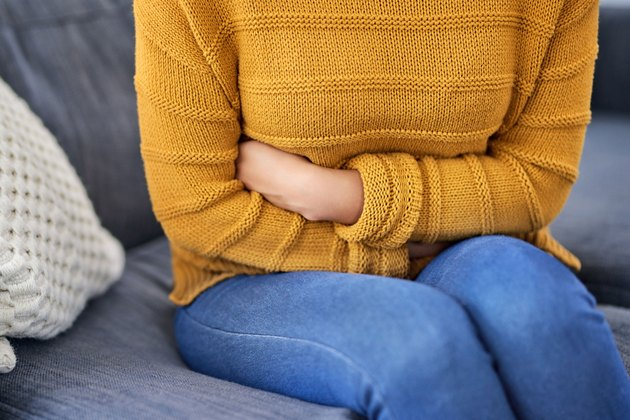 Woman sitting on a couch experiencing bloating after colonoscopy