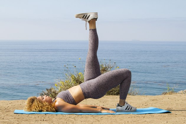 Daisha Graf doing a single-leg glute bridge on a yoga mat near the beach