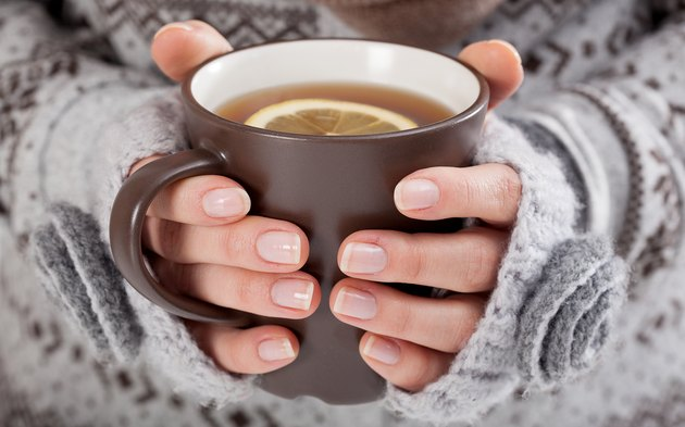 Woman hands with hot tea to soothe tonsillitis symptoms