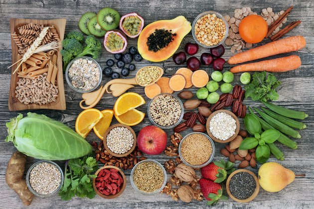 High dietary fiber health food concept with fruit, vegetables, whole wheat pasta, legumes, cereals, nuts and seeds with foods high in omega 3, antioxidants, anthocyanins, smart carbs and vitamins