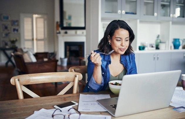 Woman eating a healthy lunch while reading on her laptop at home