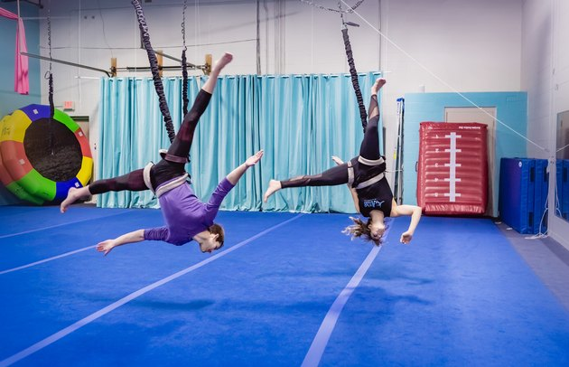 two people do an aerial flip in a gymnasium during a bungee workout class